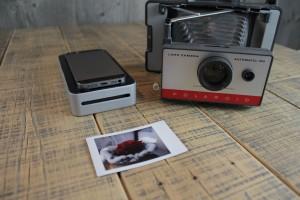 Der SnapJet neben einer alten Polaroid-Kamera