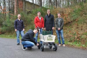 Mai-Tour-Test: Die Studenten Sergej Fabich (l.) und Matthias Hoffmann (kniend) testen mit Matthias Nienhaus (2.v.r.) und seinen Mitarbeitern Nico Haser (M.) und Robert Schwartz (r.) den Prototypen. (Foto: Saar-Uni)